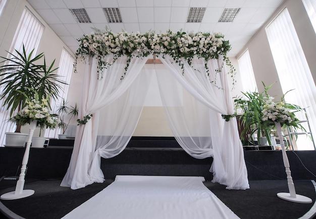 Salón decorado para una ceremonia de boda con un arco