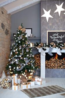 Salón decorado festivamente con chimenea y calcetines navideños. interior de la sala de navidad en estilo escandinavo. árbol de navidad con decoraciones rústicas, regalos en el ático interior. decoración del hogar de invierno