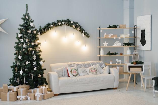 Salón decorado para navidad, un sofá y un abeto con luces.