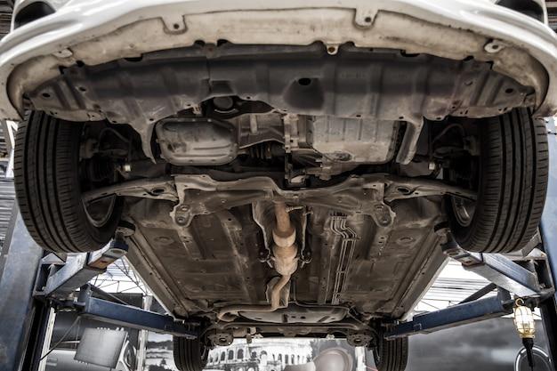 Salón espera reparación coche suspensión de automóvil levantado en la estación de servicio.