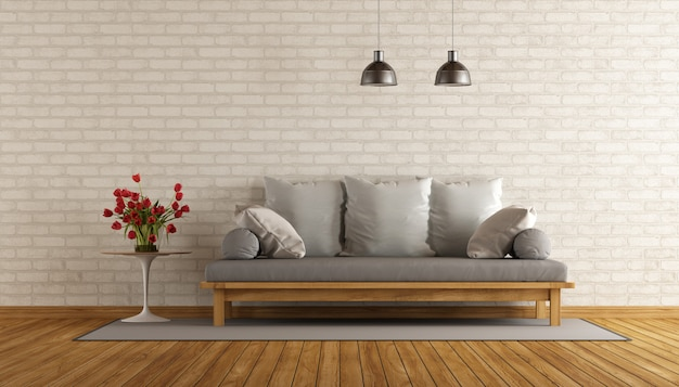 Salón con sofá de madera y pared de ladrillo.