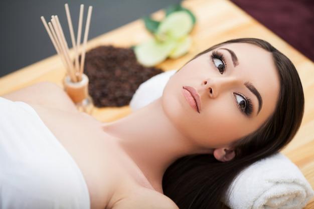 Salón de spa. joven mujer acostada sobre una mesa de masaje, relajante.