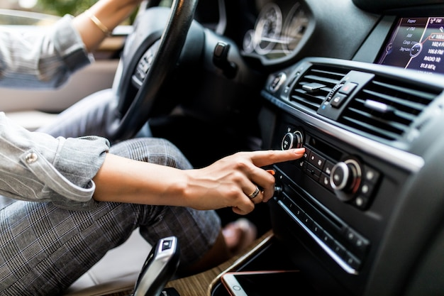 Salpicadero de coche. primer plano de radio. la mujer configura la radio mientras conduce el coche