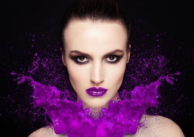 Salpicadura de pintura púrpura sobre chica de modelo de maquillaje de belleza