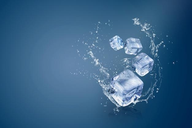 Salpicaduras de agua en cubitos de hielo aislados sobre un fondo azul y espacio de copia