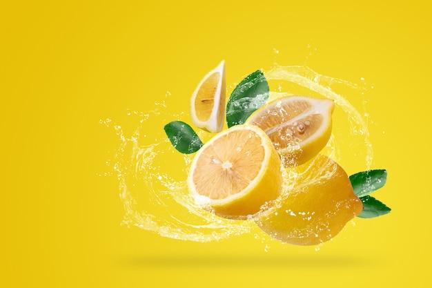 Salpicaduras de agua y fruta de limón amarillo sobre un fondo amarillo.