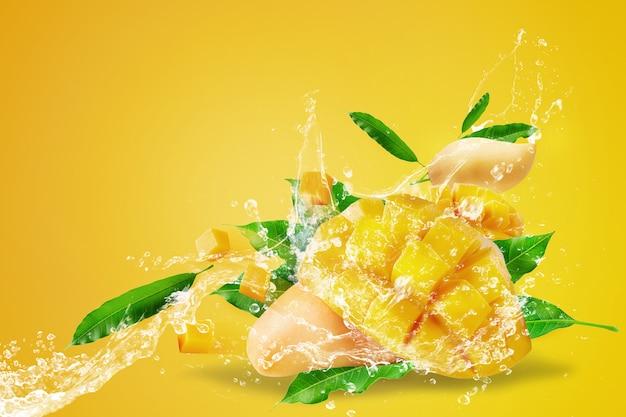 Salpicaduras de agua en fruta de mango fresco en rodajas con cubos de mango aislados en amarillo