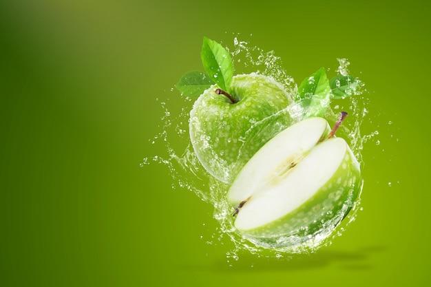 Salpicaduras de agua sobre manzana verde fresca sobre fondo verde
