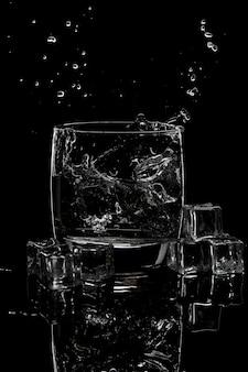 Salpicaduras de agua en un vaso de agua y hielo.