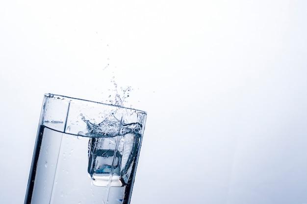 Salpicaduras de agua en un vaso de un cubo de hielo.