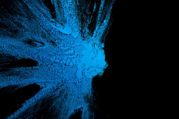 Salpicaduras de color azul sobre fondo oscuro con espacio de copia de texto