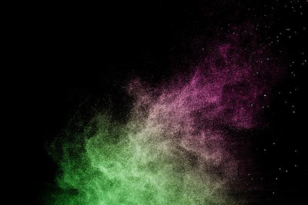 Salpicaduras de efecto de polvo verde y rosa para maquillador o diseño gráfico en fondo negro