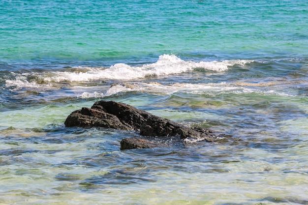Salpicaduras de olas de agua de mar golpeando la playa rocosa