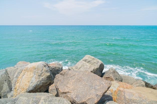 Salpicaduras de olas rompiendo contra las piedras costeras.
