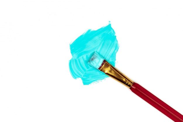 Salpicaduras de pintura azul en el centro y pincel de color rojo.