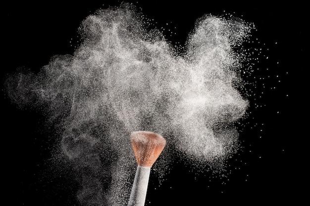 Salpicaduras de polvo blanco con maquillaje colorete cepillo aislado en negro.