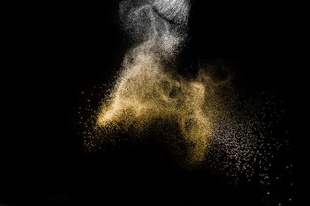 Salpicaduras de polvo dorado y pincel para el artista de maquillaje o blogger de belleza en fondo negro