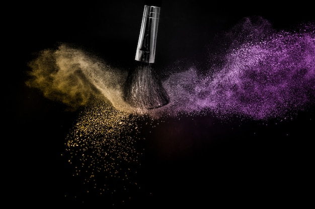 Salpicaduras de polvo de oro y púrpura en fondo negro