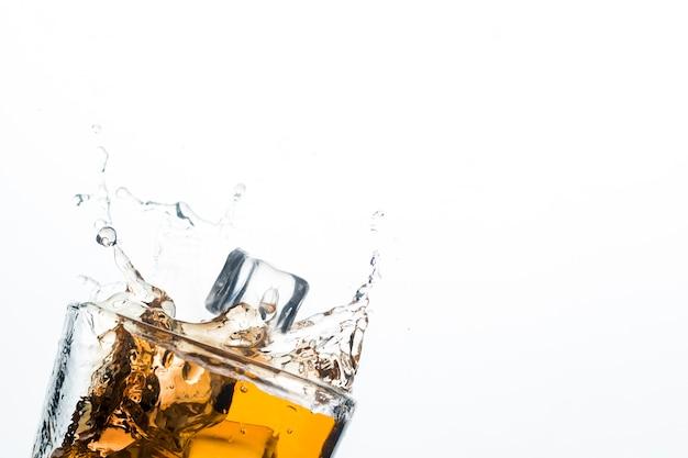 Salpicaduras de whisky de cubitos de hielo. concepto de bebidas alcohólicas con hielo, whisky o brandy, jugo de manzana y bebidas refrescantes.