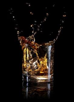 Salpicaduras de whisky de un cubo de hielo en vaso