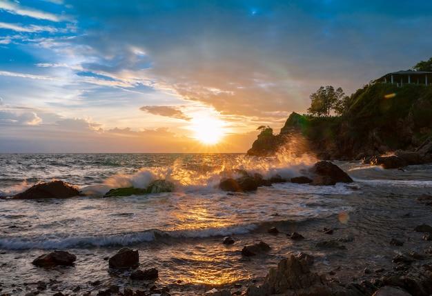 Salpicar las olas del mar en la playa de rocas con nubes de lluvia al atardecer cielo con destellos de luz con mirador de colina