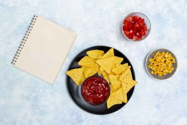 Salsa apetitosa con nachos cuaderno y verduras
