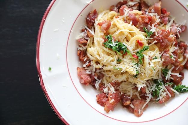Salsa blanca de espaguetis (spaghetti carbonara) con tocino y ajo, sobre fondo de mesa de madera