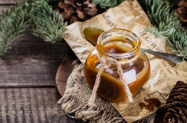 Salsa de caramelo salada casera para el postre de navidad en el frasco en la mesa de madera rústica backgrou