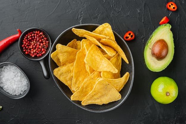 Salsa casera de guacamole y queso con nachos, sobre mesa negra, vista superior o endecha plana
