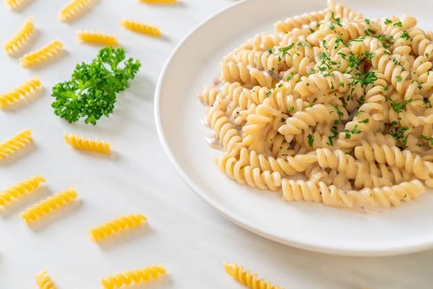 Salsa de crema de champiñones de pasta en espiral o espiral con perejil. estilo de comida italiana