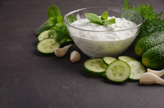 Salsa e ingredientes tzatziki. salsa fresca del pepino y del eneldo en fondo oscuro.