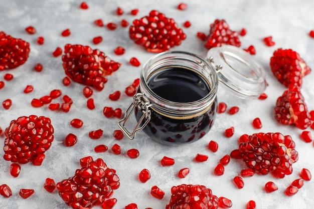 Salsa de granada dulce o jarabe para carne y pescado llamado narsharab, en un frasco de vidrio con granada purificada, enfoque selectivo