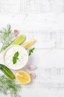 Salsa griega o aderezo tzatziki decorado con aceite de oliva y menta en una mesa de madera blanca copia espacio
