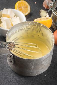 Salsa holandesa en una cacerola de metal, con ingredientes para la receta.