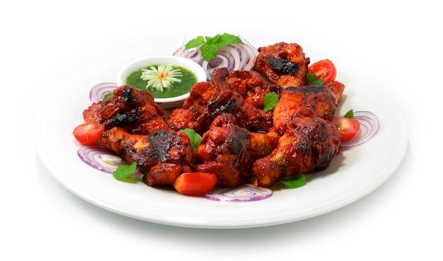 La salsa de menta servida con pollo a la parrilla tandoori es una cena india clásica que marina alitas de pollo en una base cremosa de yogur, especias mezcladas decoradas con cebolla y vegetales