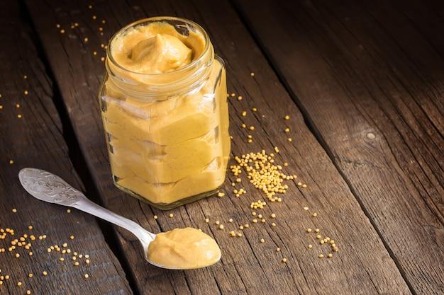 Salsa de mostaza fresca en un frasco y semillas de mostaza esparcidas