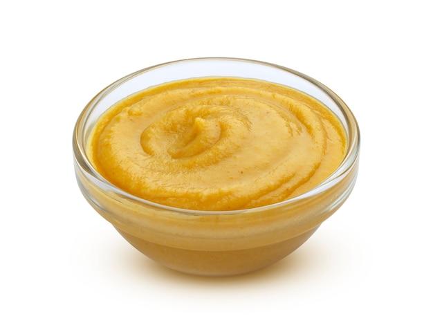 Salsa de mostaza en un recipiente aislado en blanco