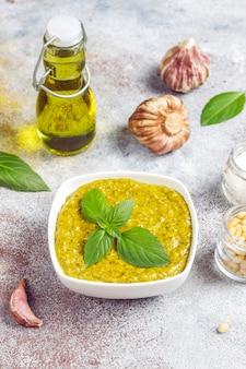 Salsa de pesto de albahaca italiana con ingredientes culinarios para cocinar.