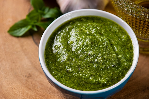 Salsa pesto en un bol con los ingredientes al fondo. aceite de oliva, ajo y albahaca.
