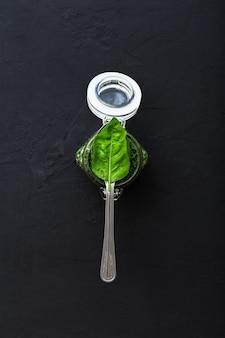 Salsa pesto casera y hojas de albahaca verde en cuchara sobre fondo de cemento oscuro.