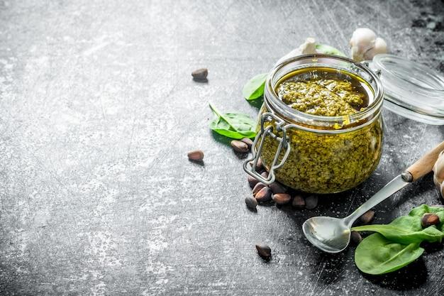 Salsa pesto en un frasco de vidrio con ajo y hierbas sobre la mesa rústica oscura