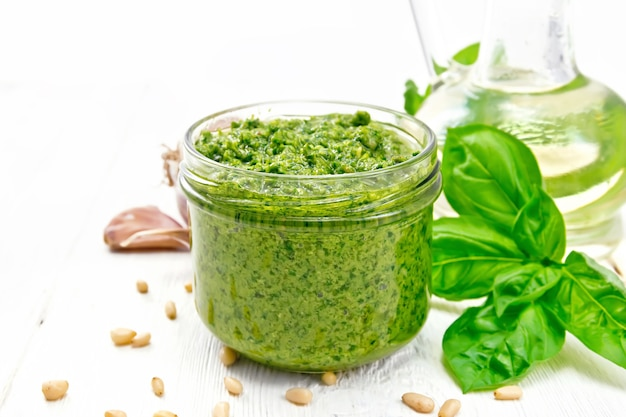 Salsa pesto en un frasco de vidrio, albahaca, piñones, ajo y aceite de oliva en una jarra en el fondo de una tabla de madera clara