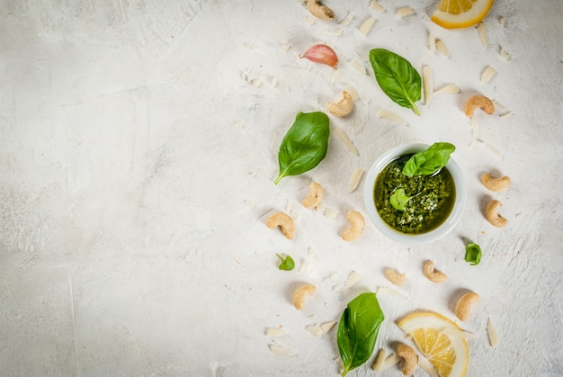 Salsa de pesto con ingredientes sobre una mesa de piedra blanca