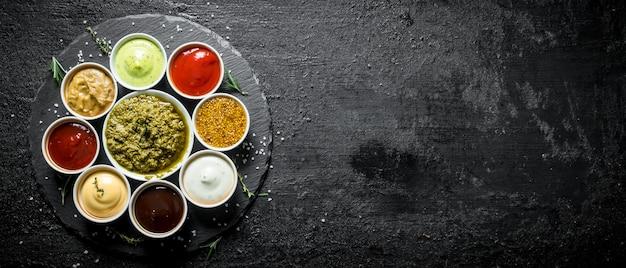 Salsa pesto, salsa de tomate, salsa barbacoa, mostaza, mayonesa, salsa guacamole sobre una tabla de piedra.