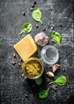 Salsa pesto en un tarro con albahaca, dientes de ajo y parmesano. en mesa rústica oscura