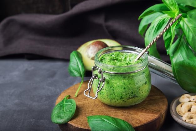 Salsa de pesto vegano casera fresca con albahaca, espinacas, anacardos y aguacate en tarro de hormigón gris con ingredientes