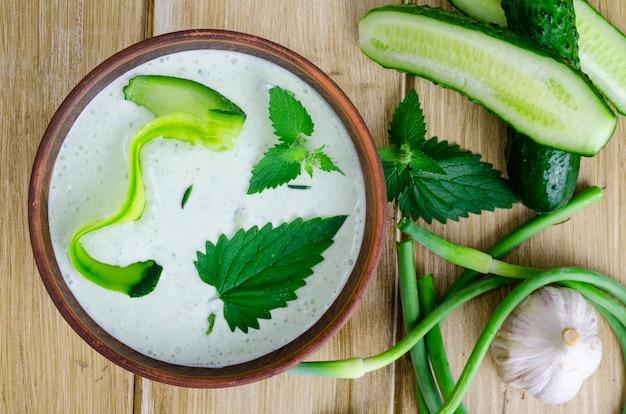 Salsa de salsa griega tradicional o aderezo tzatziki preparado con pepino rallado, yogur, aceite de oliva y eneldo fresco en una mesa de madera en un tazón de cerámica.