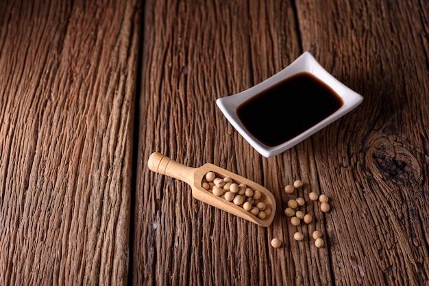 Salsa de soja con la haba de soja en fondo de madera.