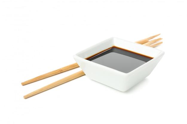 Salsa de soja y palillos aislados sobre fondo blanco.