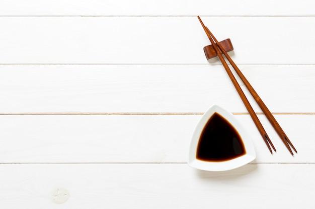 Salsa de soja con palillos en mesa de madera blanca